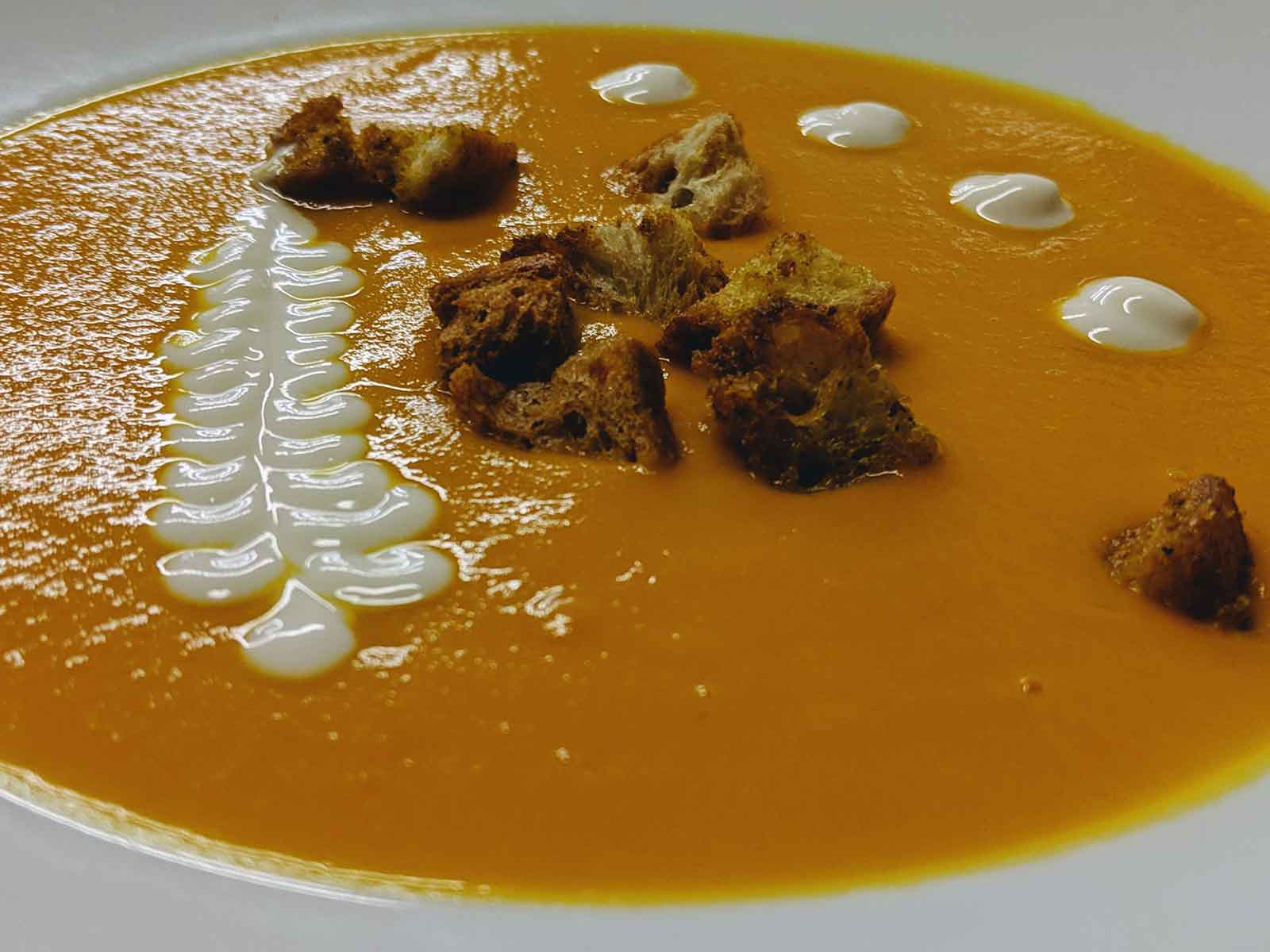 Cream of carrot and coconut soup and croutons with curry